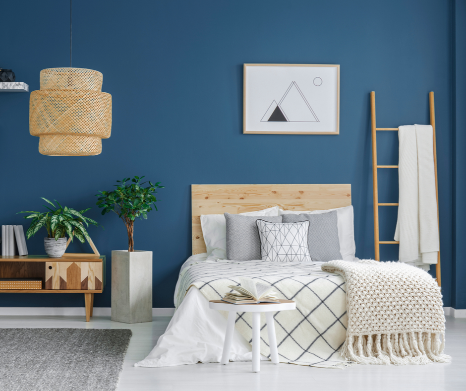 A modern bedroom utilizing 2020 themed colors to include stormy blue walls, grey planters, and a natural wood headboard.